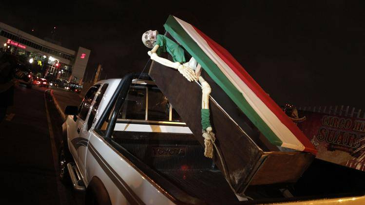 A Costa Rica fan displays a coffin, draped with the Mexican flag with a skeleton partially sticking out from it, on the back of his pickup truck outside the National Stadium before a practice session for Mexico's national soccer team in San Jose, Monday. Mexico will face Costa Rica October 15 in a qualifying match for World Cup 2014 in Brazil. REUTERS/Juan Carlos Ulate