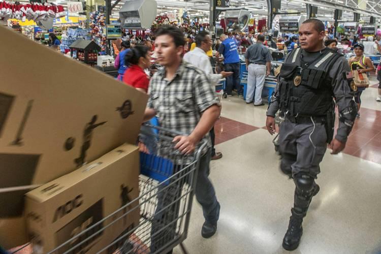 At the Walmart store in San Sebastian (San José) an armed security guard escorts a customer.  | Photo: La Naciona, FABIÁN HERNÁNDEZ.