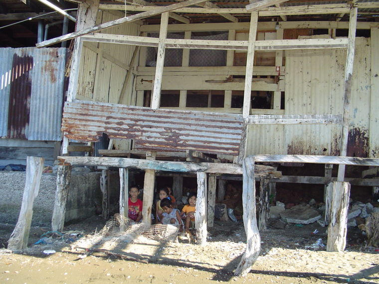 Children play in the shade of an abandoned building in Costa de Pajaros.