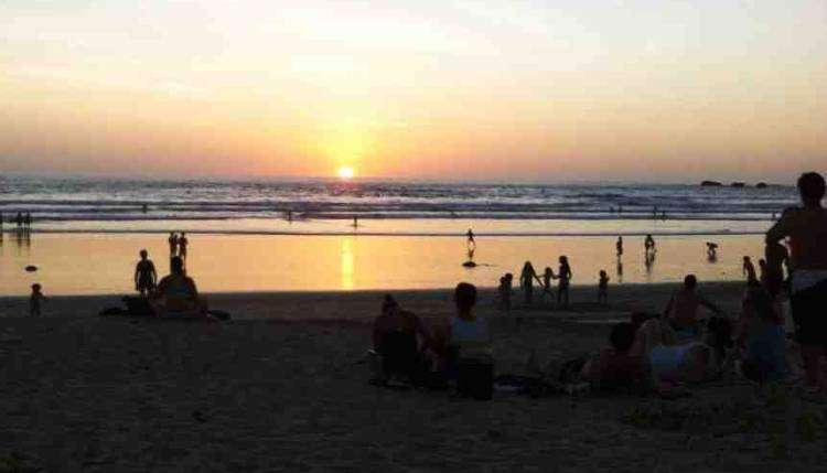 Tourists enjoying sunset at year's end  a Guiones Beach. Photo by Patricia Jimenez