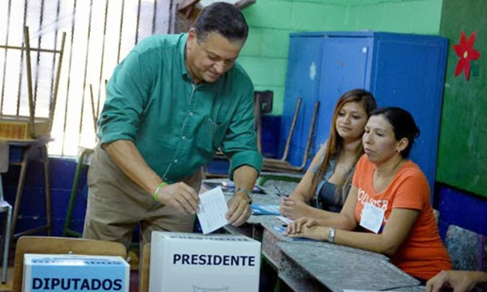 Vote counters stand by while presidential candidate Johnny Araya casts his vote.