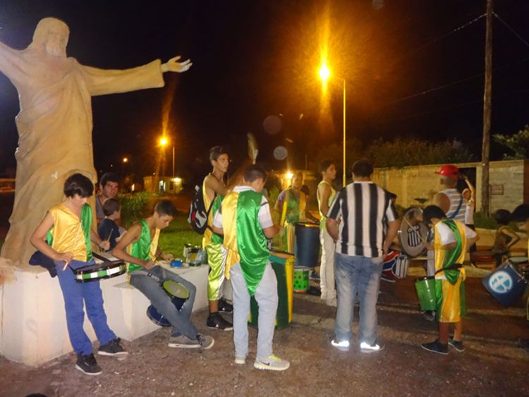 Musicians of the Colour and Joy group tuning drum heads next to a replica of the statue of Christ the Redeemer. Credit: Fabiana Frayssinet/IPS
