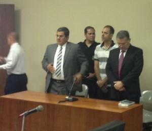 Quesada, in a striped polo shirt, stands to hear the sentence by the Tribunal Penal de Hacienda.