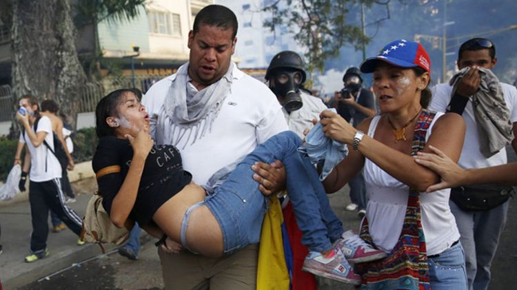 Demonstrators help a girl overcome by tear gas as protest against the government of President Maduro in Caracas, February 22, 2014. The government arrested one of the main opposition leaders and several student activists. (Reuters/Carlos Garcia Rawlins/Via Cbc.ca