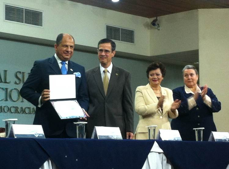 President-elect Luis Guillermo Solís (left) received his credential from TSE president, Luis Antonio Sobrado, The prez to be also celebrated his 57th birthday on Friday.