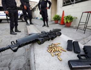 Salvadoran police officers guard an M16 rifle and a gun that were recently confiscated from gang members after an operation by the Anti-Gang Unit of the National Civil Police (PNC) in the district of El Tránsito in the municipality of Cuscatancingo. (Francisco Campos for Infosurhoy.com)