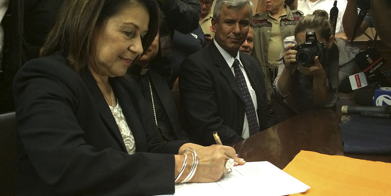 Education Minister, Sonia Marta Mora, signs the agreement that puts and to the month long strike by teachers.