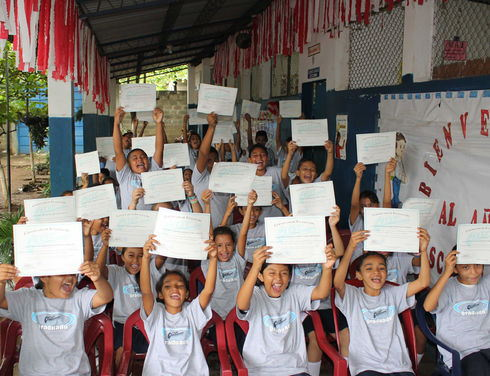 """Students at Cantón el Ojushte School in El Salvador's Usulután department display their certificates of participation in the """"Educating Resistance and Gang Membership by Children and Youths"""" program. (Gloria Cañas for Infosurhoy.com)"""