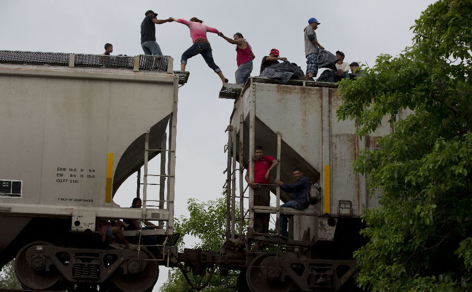A woman is helped from one boxcar to another, as Central American migrants wait atop the train they were riding north. (Rebecca Blackwell/AP)