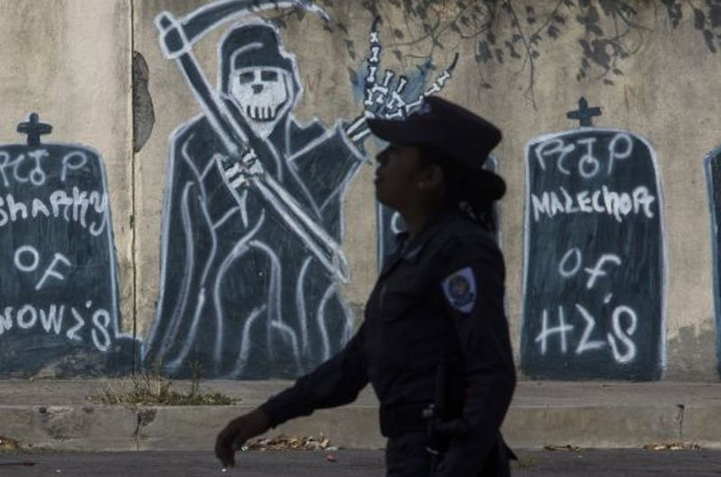 In this April 14, 2014 file photo, a police officer walks past graffiti depicting gang members that have died during a patrol in a neighborhood controlled by the Mara Salvatrucha gang in Ilopango, El Salvador. In El Salvador, the end of a truce between street gangs has led to a steep rise in homicides this year adding impetus to the migration of youths and children to the U.S. (AP Photo/Salvador Melendez, File)