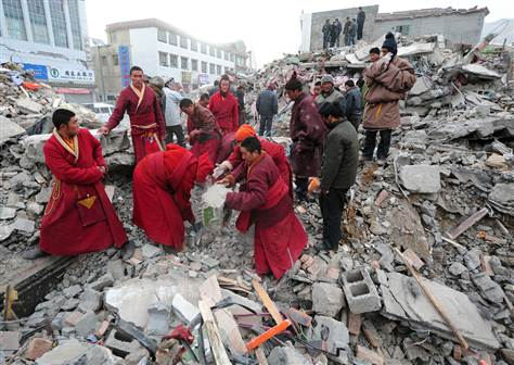 Tibetan Buddhist monks clear debris while searching for survivors amid a collapsed apartment block in Jiegu, China on Friday.