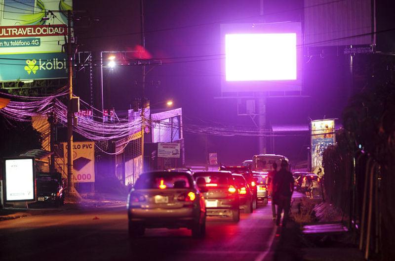 Driving north from La Uruca to Herdia, at the winding curve before the Rio Virilla bridge, drivers at night cannot help but focus on the big screen.   Photo: Gabriela Tellez, La Nacion