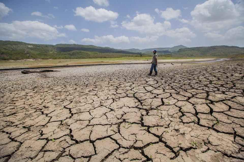 A man crosses the reservoir of Las Canoas, 60 km from Managua, on July 30, 2014