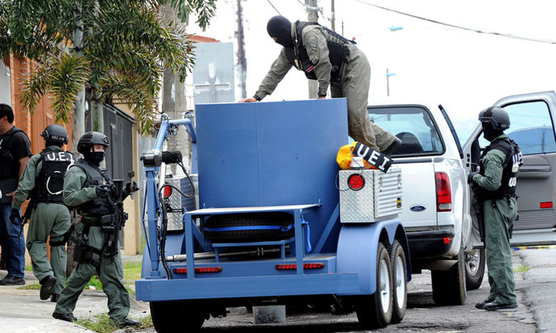 Specialized police unit recover weapons arsenal from Heredia home on Friday.