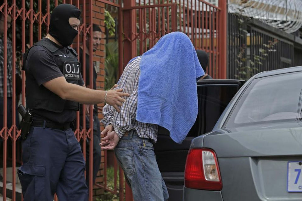 Sibaja (under the towel) being led out his home in Cipreses de Curridabat by Judicial agents on Tuesday,