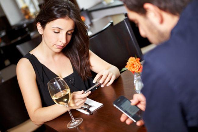 Paar im Restaurant schaut auf Handys