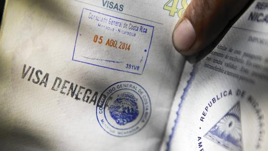 """A man shows his passport with a """"visa denied"""" stamp, outside the Costa Rican consulate in Managua, Nicaragua, where he stood in line for two days. (Esteban Felix / Associated Press)"""