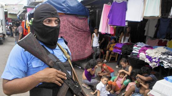 A police officer patrols a market during an anti-drug operation in a market street in Managua, Nicaragua. (Esteban Felix / Associated Press)