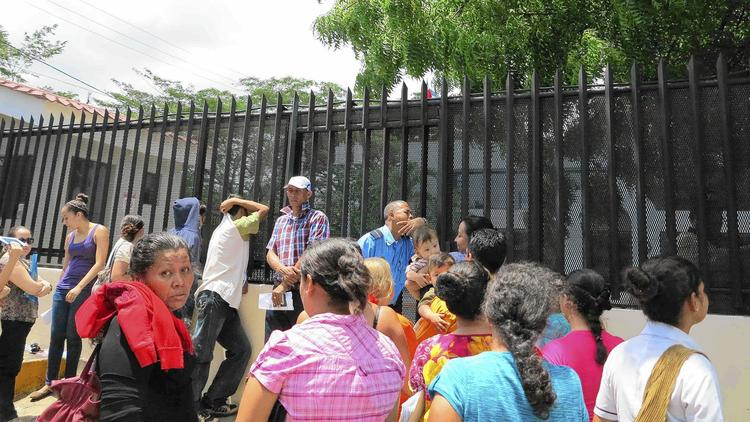 A small crowd gathers outside the Costa Rican consulate in Managua, Nicaragua on Aug. 8, 2014. Most weekdays see scores of Nicaraguans seeking a Costa Rican visa. (Tim Johnson / McClatchy-Tribune)
