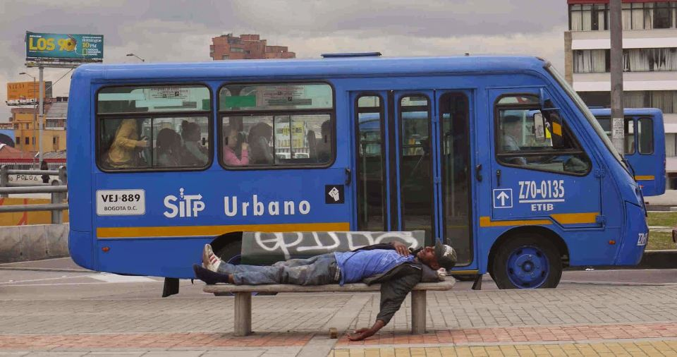 A SITP bus with an impressive number of passengers. (The man on the bench is displaying his solidarity with the bus strike.)