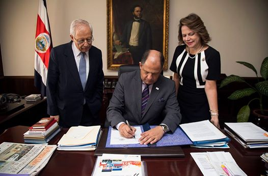 President Solís, accompanied by his vice-presidents is seen signing the bill. Foto: Casa Presidencial