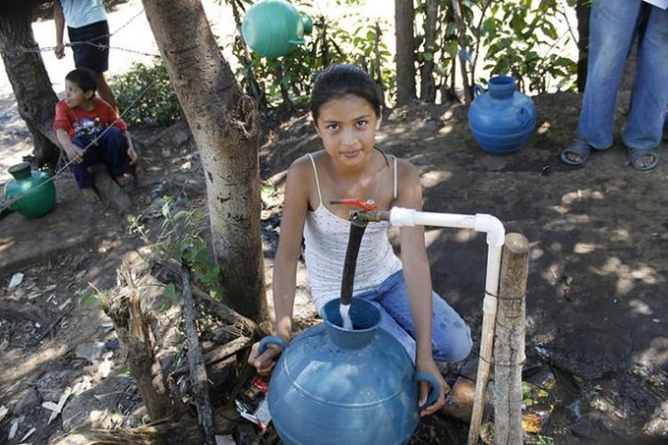 Jeniffer Hernández, 12, fills her water jug at the community tap in the village of Los Pinos in the municipality of Tacuba in western El Salvador. This is one of the taps where those who have no piped water in their homes have free access to water. Credit: Edgardo Ayala/IPS