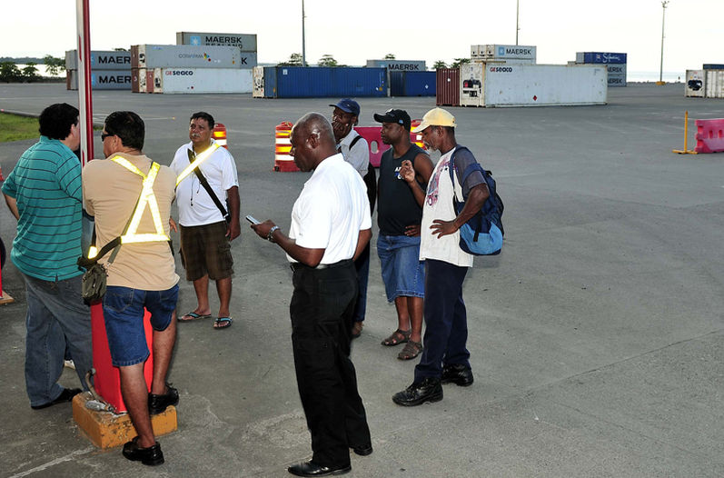 Striking dockworkers with containers in the background. Photo La Nacion, John Durán
