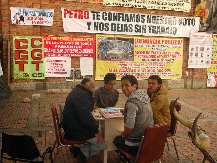 Bullfighting supporters play a board game.
