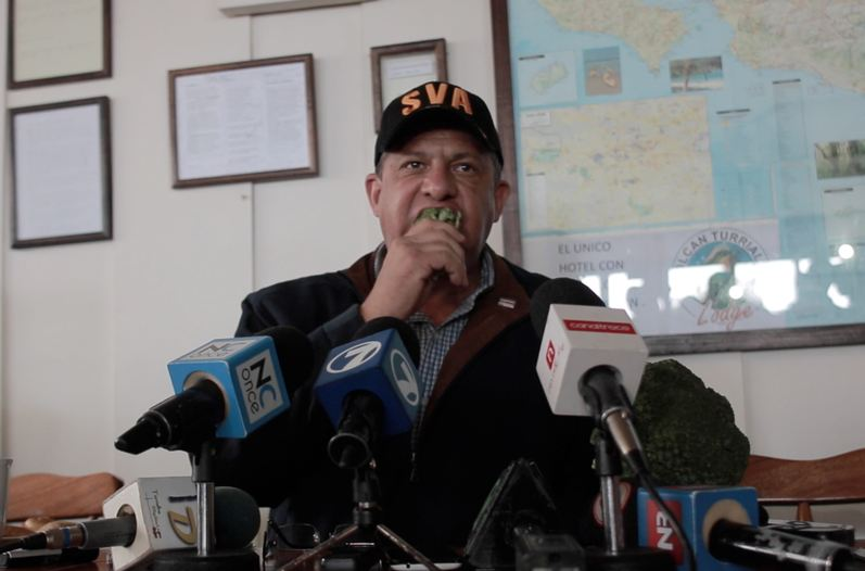 President Luis Guillermo Solís, in front of cameras, takes to eating broccoli grown locally in the area of the Turrialba volcano.