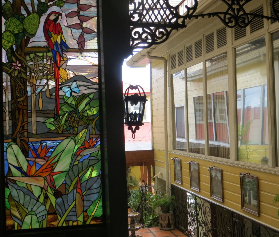 Ornate wrought-iron lamps and lattice work set off this colorful stain-glass window