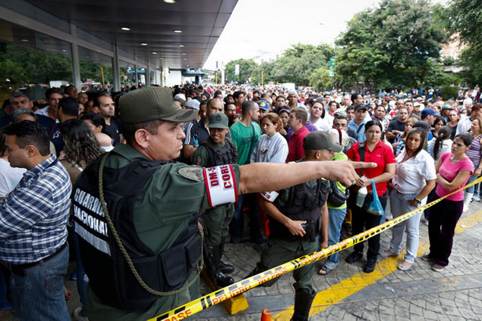 Venezuelan-soldiers-control-the-crowd-as-people-wait-to-shop-for-electronic-goods-outside-a-Daka-store-in-Caracas