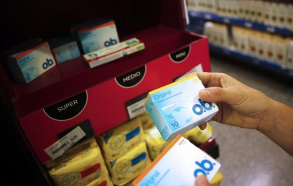 A woman takes tampon boxes out of a supermarket shelf in Buenos Aires January 16, 2015. Credit: REUTERS/Marcos Brindicci