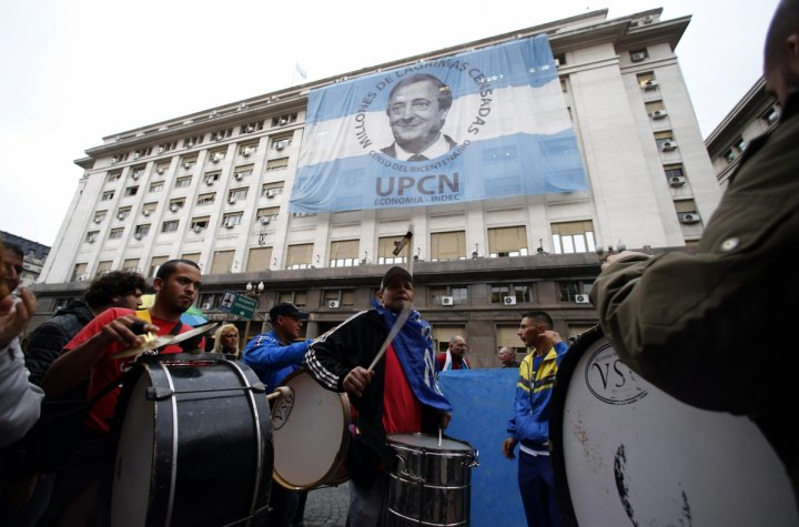 Pro-government demonstrators beat drums in front of an image of late President Nestor Kirchner placed over the Economy Ministry in Buenos Aires financial district. Reuters