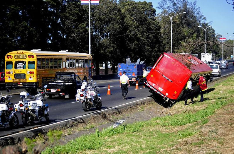 The bus took down a sign pos and landed in the ditch (cuneta in Spanish) on the autopista General Cañas. Photo Alexánder Caravaca, La Nacion