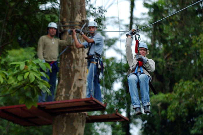 Dutch tourist Carolyn Dorsman, right, rides through the canopy of the tropical forest as her husband, Wim Dorsman, left, and Costa Rican guide Esteban Cedeno, center, look on at the Arenal Volcano near La Fortuna, Costa Rica, north of the capital of San Jose. Zip lining through the Costa Rican rainforest is an extremely popular pursuit among tourists. [The Associated Press]
