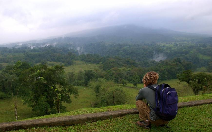 Majestic view: An American tourist looks out over cloud-covered Arenal Volcano near La Fortuna, Costa Rica. | AP