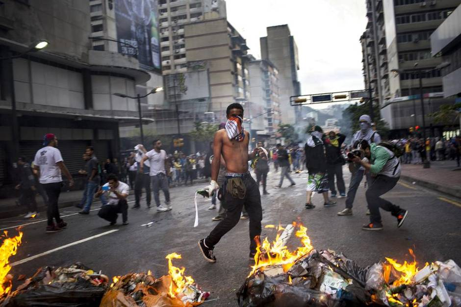 Protesters burn barricades and hurl Molotov cocktails in Chacao on the anniversary of the start of last year's protests. (Natalie Keyssar for The Globe and Mail)
