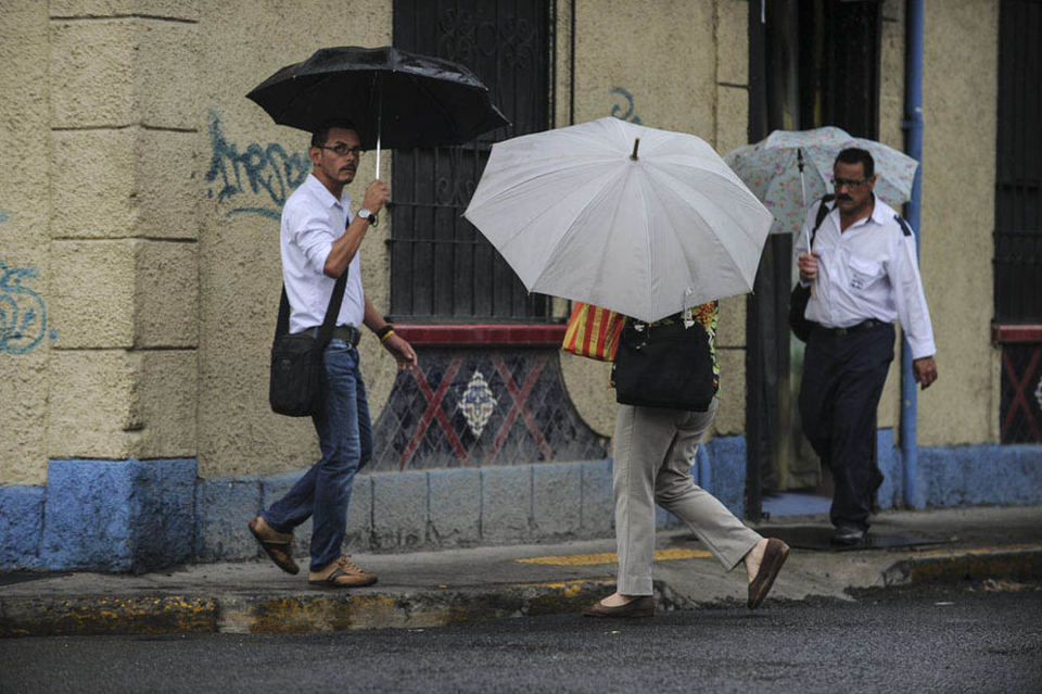 Umbrellas were the norm Monday afternoon in San Jose. Photo by Jorge Navarro, La Nacion, in Barrio Amon