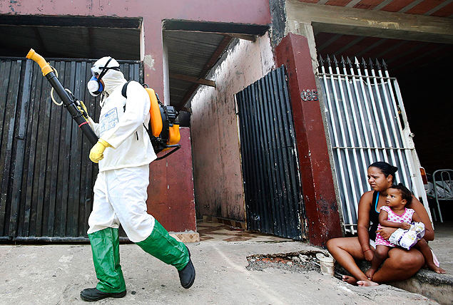 A health official walks past residents as he carries out fumigation to help control the spread of dengue fever in Sao Paulo