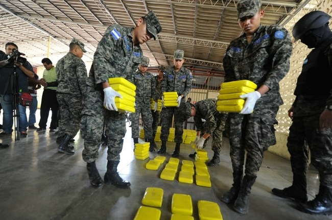 Soldiers display packages containing 450 kilograms of cocaine on April 23 in Tegucigalpa. Security forces seized the drugs in La Mosquitia. [Photo: AFP/Orlando Sierra]