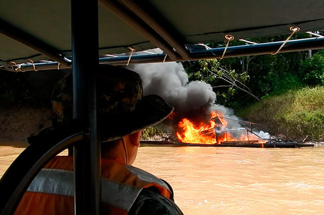 Service members of the Peruvian Navy, in coordination with other government authorities, destroy machinery and equipment that criminals use to illegally extract gold along the Amazon River. [Photo: Peruvian Navy]