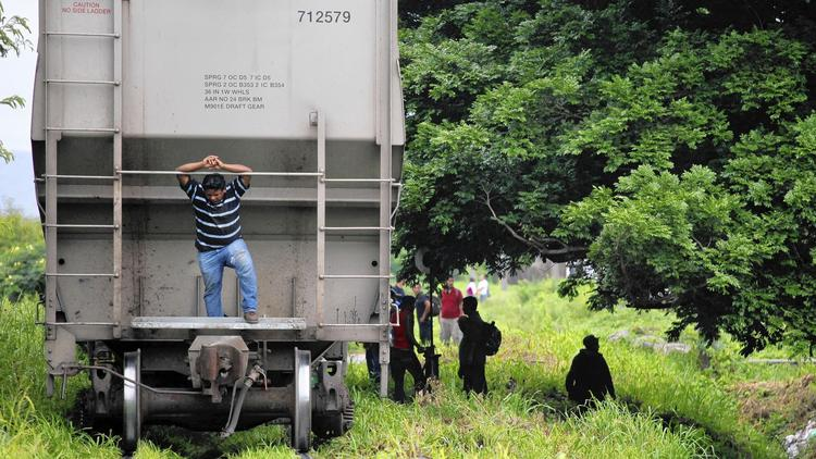 """Migrants wait to board """"La Bestia"""" outside Arriaga. Mexico has deported more than 60,000 Central American migrants in its crackdown this year, perhaps half of those in recent months, officials say. (Michael Robinson Chavez / Los Angeles Times)"""