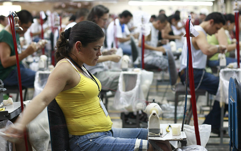 A Rawlings employee sews baseballs for use at the 2010 Major League Baseball tournament at a factory in Turrialba, Costa Rica