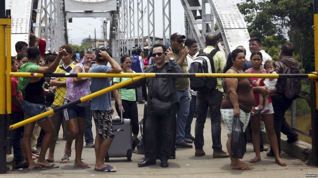 People stand next to a closed gate as they wait to try to cross La Union international bridge, on the border with Colombia at Boca de Grita in Tachira state, Venezuela, Aug. 29, 2015