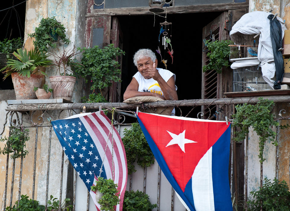 A Cuban gives the thumbs up from his balcony decorated with the US and Cuban flags in Havana. AFP PHOTO/YAMIL Lage (Photo credit should read YAMIL LAGE/AFP/Getty Images)