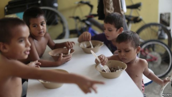 """Honduran children have meals at the Todo por ellos (All for Them) immigrant shelter in Tapachula, Chiapas, in southern Mexico, June 26, 2014. 