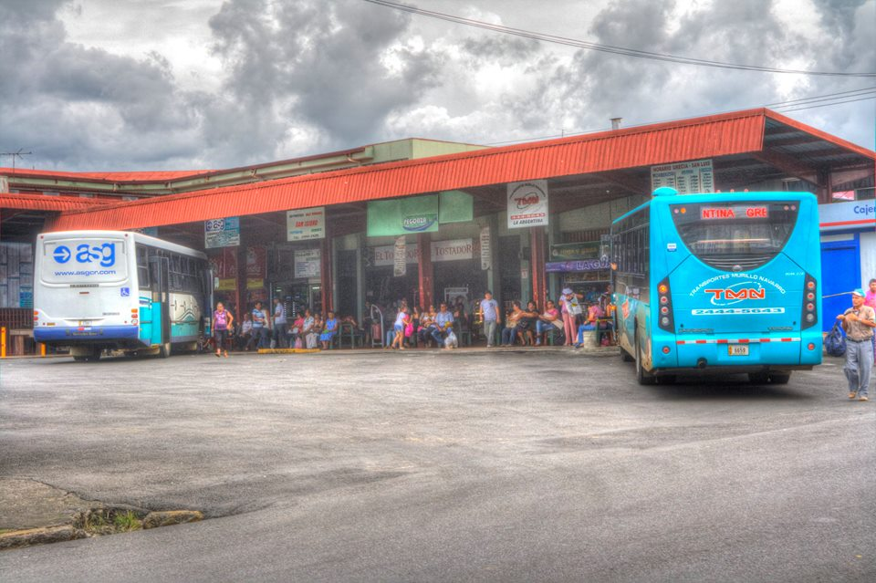 Riders wait at the city bus station in Grecia.