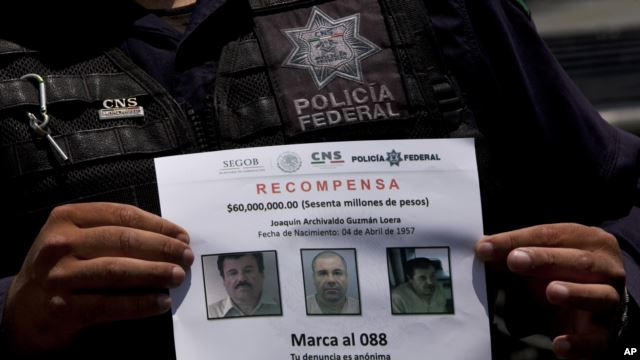 """FILE - In this July 16, 2015 file photo, a Federal Police shows a reward notice for information leading to the capture of drug lord Joaquin """"El Chapo"""" Guzman, who made his escape from the Altiplano maximum security prison via an underground tunnel, in Al"""