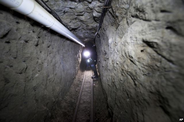 """FILE - Federal Police officer stands in the tunnel where according to authorities drug lord Joaquin """"El Chapo"""" Guzman made his escape from the Altiplano maximum security prison in Almoloya, July 16, 2015."""
