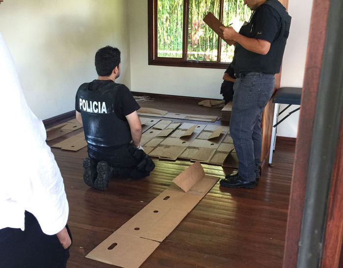 Police with evidence of the boxes used to hide the illegal drugs in shipments of yuca and pineapple. Photo Ministerio de Seguridad Publica